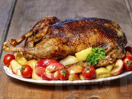 Сочна печена пълнена новогодишна патица с картофи и сос от боровинки и портокали на фурна - снимка на рецептата